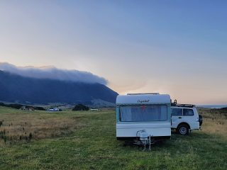 Caravan overlooking coastal cliffs in New Zealand at sunrise