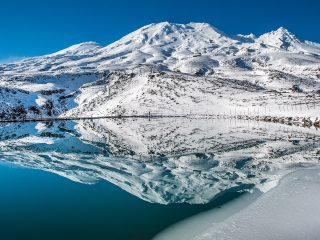 Mt. Ruapehu reflected in the blue waters of a mountain lake
